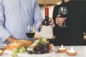 Zwei Personen mit Rotweingläsern mit eingeschenktem Rotwein plus eine flasche offener Rotwein